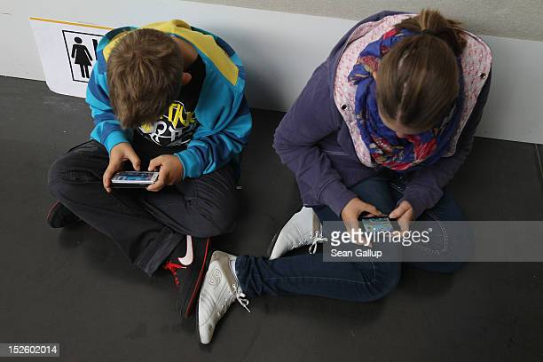 Children play video games on smartphones while attending a public event on September 22 2012 in Ruesselsheim Germany Smartphones with their access to...