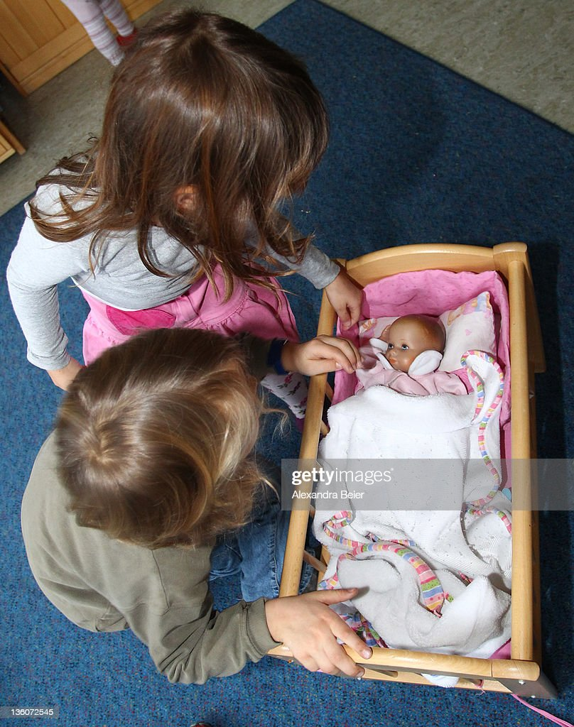 Children play with a baby doll at a day care center for children aged 12 months to six years on December 22, 2011 in Munich, Germany. German authorities claim the country will need to increase the capacity of its child day care centers by at least an additional 230,000 by 2013.