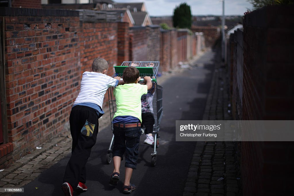 Children play with a discarded shopping trolley in the back alleys of Summerbank in Tunstall as the school Summer holidays begin on July 26 2011 in...