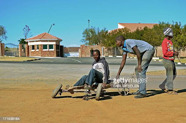 Children play with a gokart outside the house of fFormer South African president in Qunu on June 26 2013 Mandela's close family members gathered to...