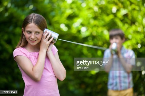Children play with a tin can telephone. : Stock Photo