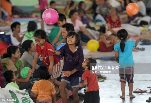 Children play with balloons after being evacuated during the raised alert levels for the volcano on Mount Agung in Klungkung regency on the...