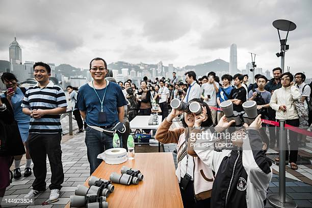 Children play with binoculars as people wait to catch a glimpse of an eclipse obscured by heavy clouds in Hong Kong on May 21 2012 The path of the...