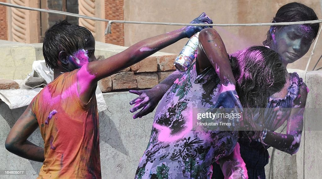Children play with colours during Holi festival celebration on March 27, 2013 in New Delhi, India. Holi, festival of color is Hindu religious festival also called Basantotsav or spring festival as it mark the arrival of spring. People gather together to play colors, sing and dance to traditional tunes and eat sweets specially Gujiyas.