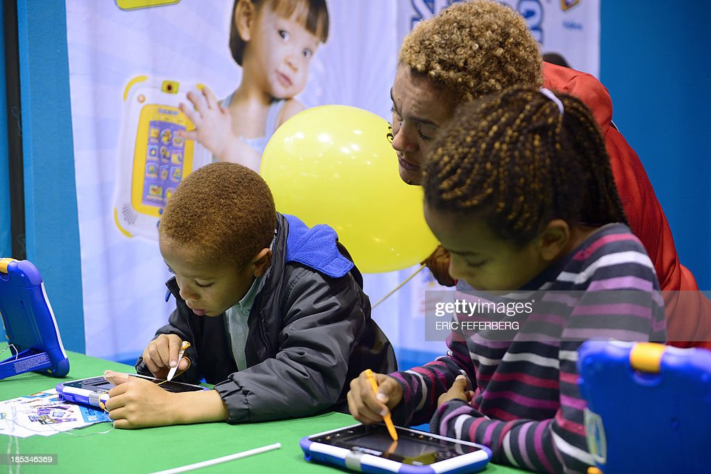 Children play with digital tablets on October 19, 2013, during the 'Kidexpo' show at the Porte de Versailes exhibition centre in Paris. This family event, running until October 23, offers workshops and discovery areas to children aged from four to fourteen years old. AFP / PHOTO / ERIC