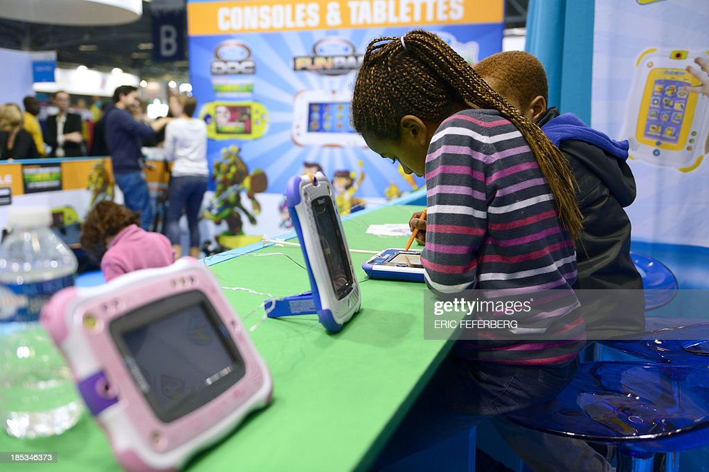 Children play with digital tablets on October 19, 2013, during the 'Kidexpo' show at the Porte de Versailes exhibition centre in Paris. This family event, running until October 23, offers workshops and discovery areas to children aged from four to fourteen years old. AFP / PHOTO / ERIC FEFERBERG