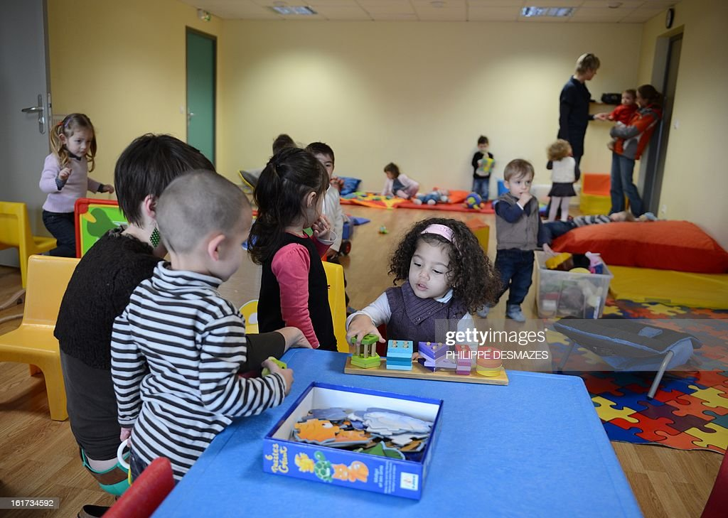 Children play with employees in a creche of the Karapat association on February 8, 2012 in Lovagny.
