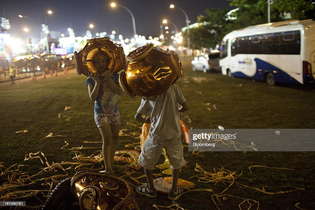 Children play with items from discarded costumes outside the Sambadrome during Carnival celebrations in Rio de Janeiro, Brazil, on Monday, Feb. 11, 2013. The festivities, which are expected to attract almost 900,000 visitors, precede the start of Lent, which begins with Ash Wednesday on Feb. 13. Photographer: Dado Galdieri/Bloomberg via Getty Images