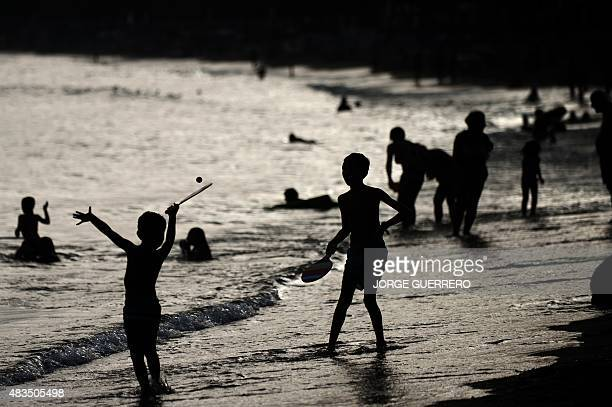 Children play with rackets and a ball on the shore at Marbella beach on August 9 2015 AFP PHOTO/ JORGE GUERRERO