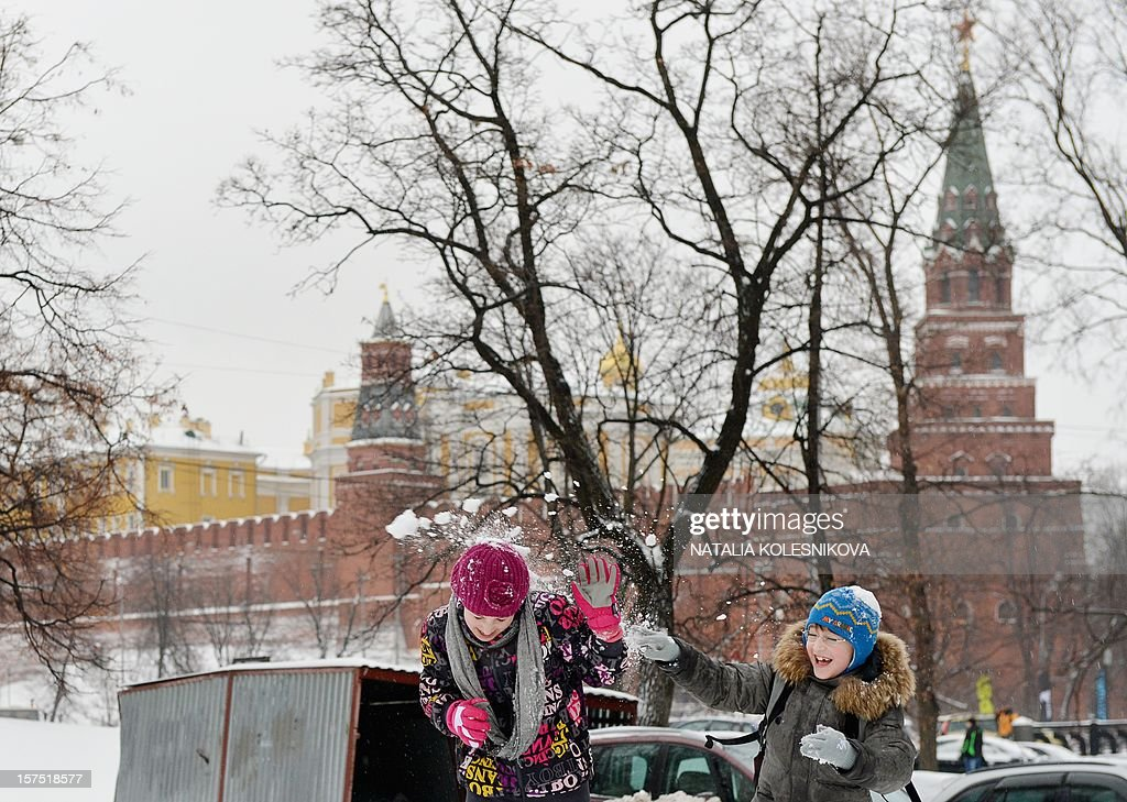 Children play with snow just outside the Kremlin in Moscow, on December 4, 2012. Moscovites woke up today to a thick blanket of snow covering the Russian capital.The temperatures in Moscow reached today 1C (34 F), but due to high humidity and wind, weather experts said it would feel more like - 3C (25 F).