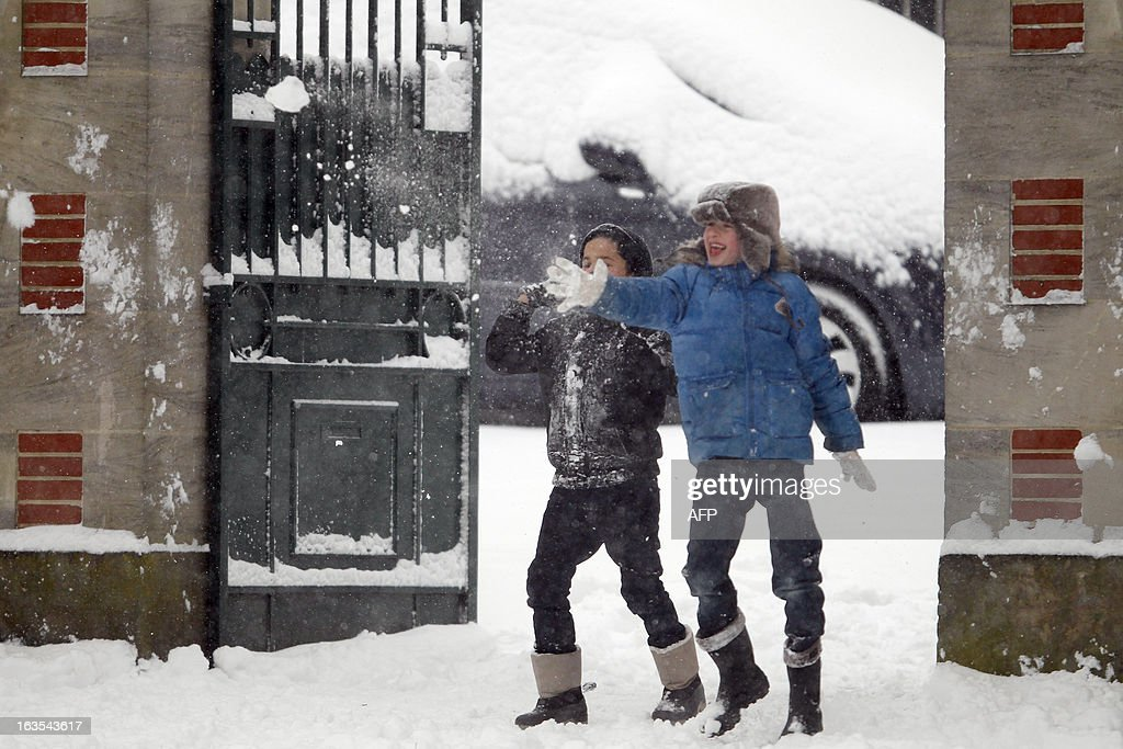 Children play with snow on a snowy sidewalk, on March 12, 2013 in Caen, northwestern France, during a heavy snow storm on France. Overnight Monday nearly 500 cars were blocked near Cherbourg where snowdrifts piled up 60 centimetres (almost two feet) as winds reached 100 kilometres (more than 60 miles) an hour. Twenty-six regions in northwest and northern France were put on orange alert because of heavy snowfalls, which Meteo France said were 'remarkable for the season because of the expected quantity and length of time'.