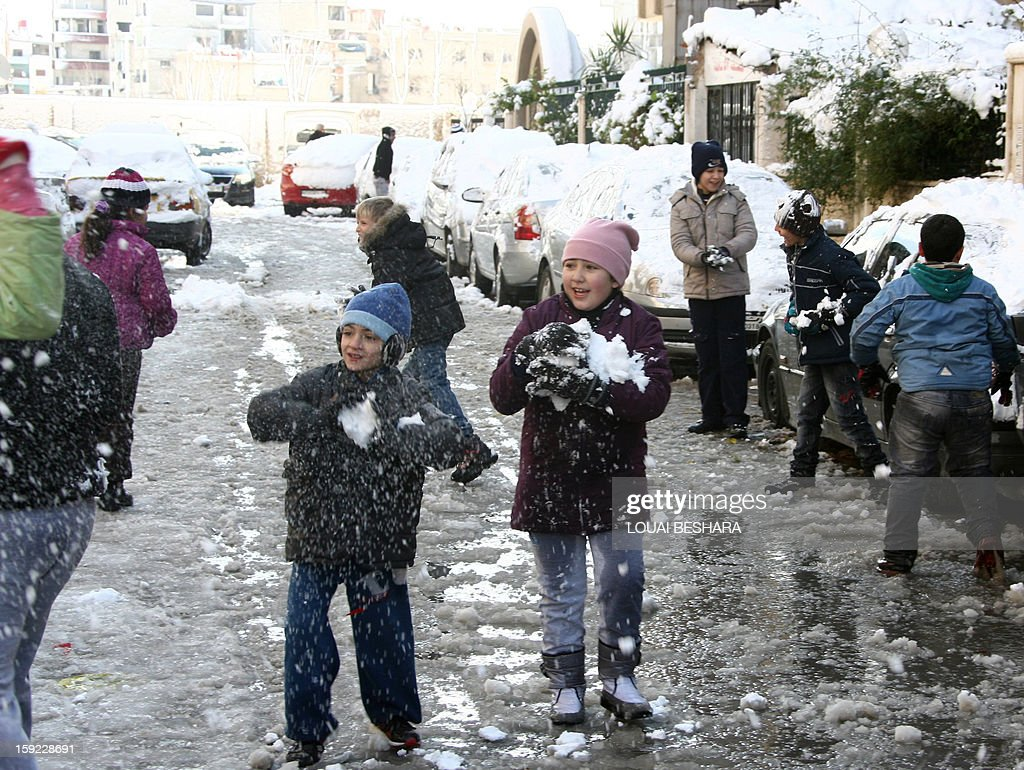 Children play with snow on January 10, 2013 in the Syrian capital of Damascus. Snow carpeted Syria's war-torn cities but sparked no let-up in the fighting, instead heaping fresh misery on a civilian population already enduring a chronic shortage of heating fuel and daily power cuts.