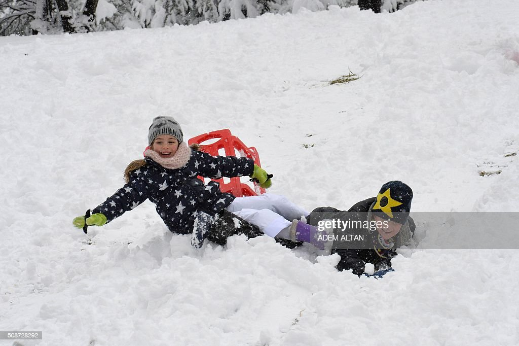 Children play with the snow in Ankara on February 6, 2016. / AFP / ADEM ALTAN