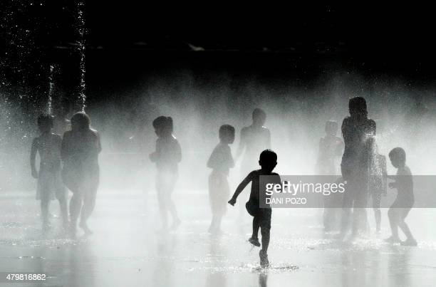 Children play with the water of fountains on the banks of the Manzanares river in Madrid on July 7 2015 In Spain started on July 1 2015 a new...