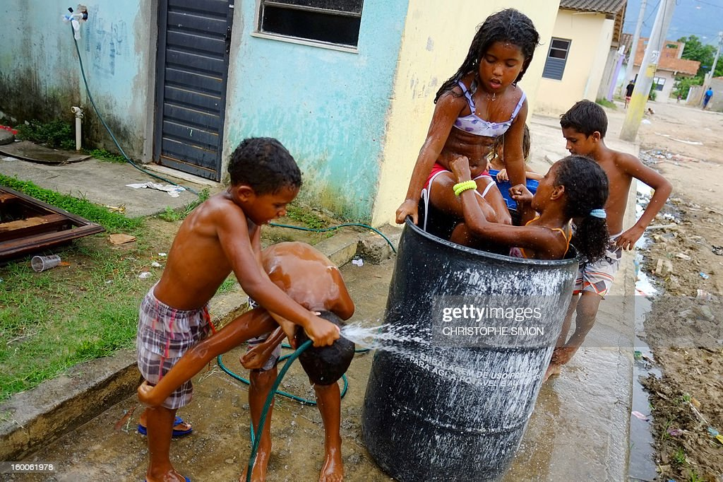 Children play with water at Cidade de Deus slum in Rio de Janeiro, Brazil on January 25, 2013.