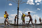 Children play with water in a park at the Russian leased Baikonur cosmodrome on July 7 2016 The temperature reached 36 degrees centigrade / AFP /...