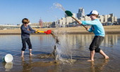 Children play with water on the Scheveningen beach on March 5 2014 Spring like weather is expected in the country for the next week AFP PHOTO / ANP...