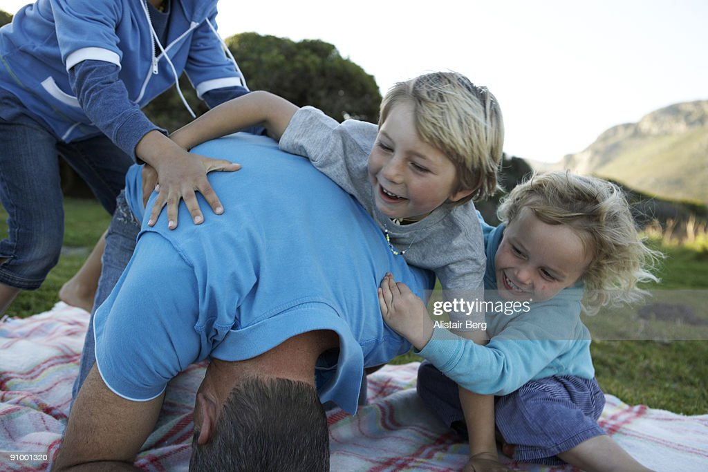 Children play wrestling with their dad : Stock Photo