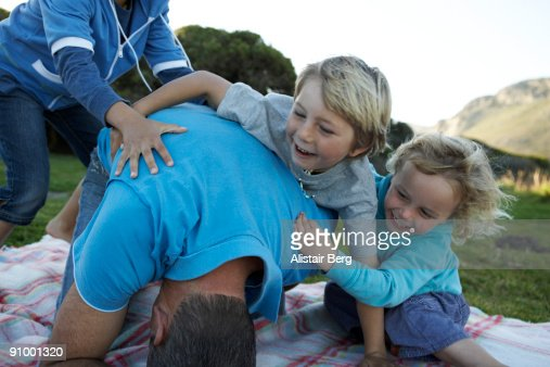 Children play wrestling with their dad : Bildbanksbilder