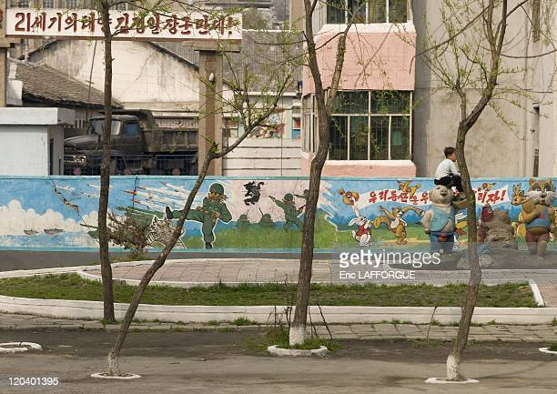 Children playground with a war fresco in North Korea A north korean fox fights and kills a wolf