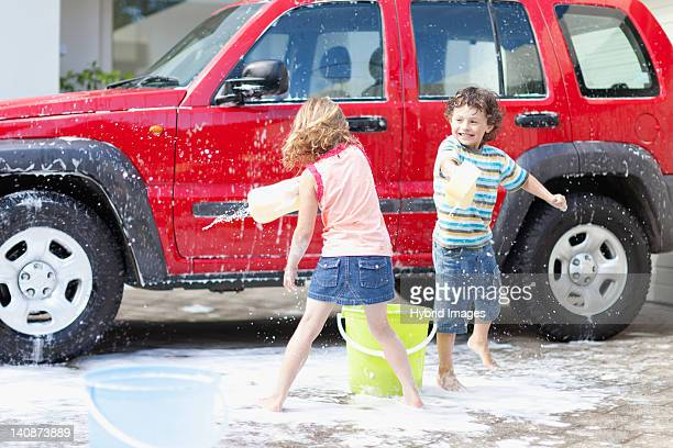 Children playing and washing car