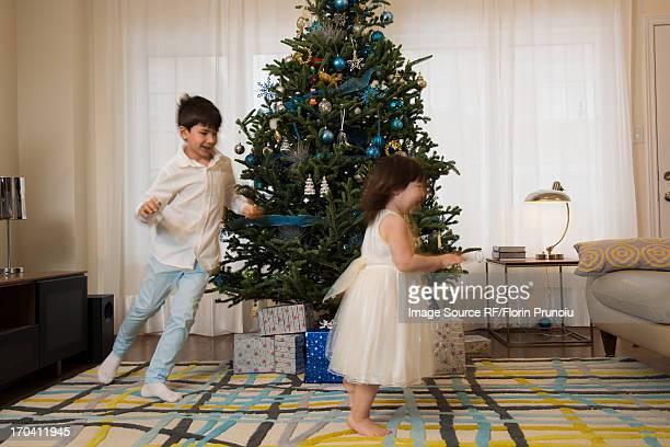 Children playing around Christmas tree