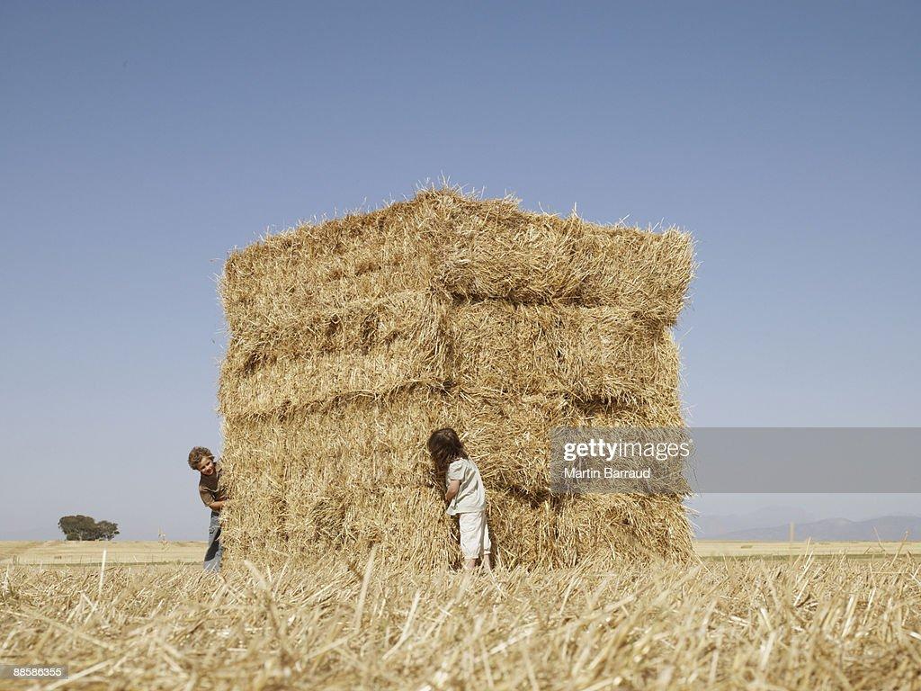 Children playing around hay bales
