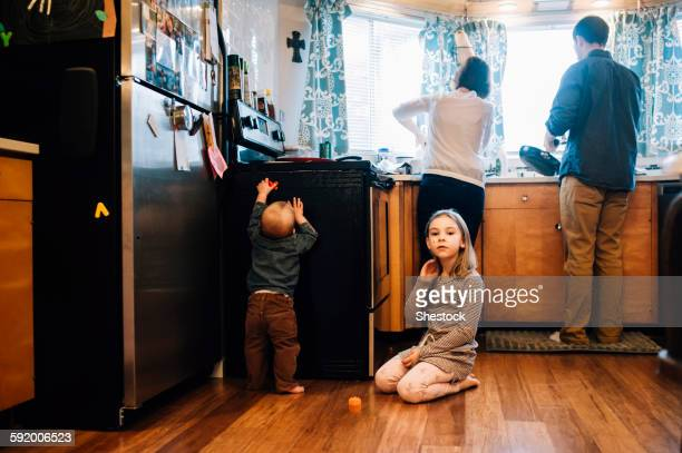 Children playing as parents cook in kitchen