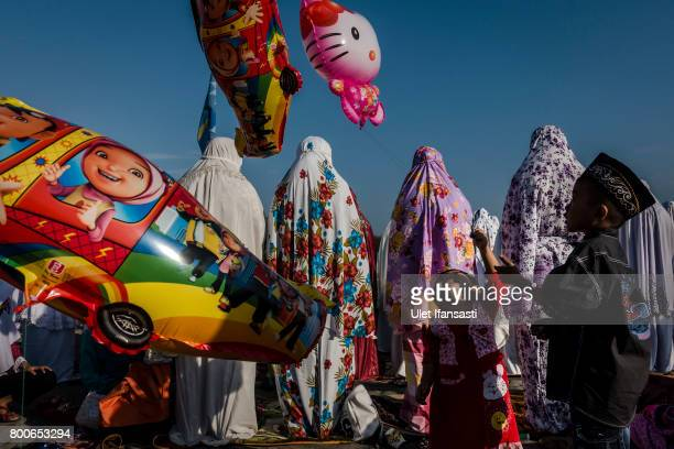 Children playing balloons as Indonesian Muslims perform Eid AlFitr prayer on 'sea of sands' at Parangkusumo beach on June 25 2017 in Yogyakarta...