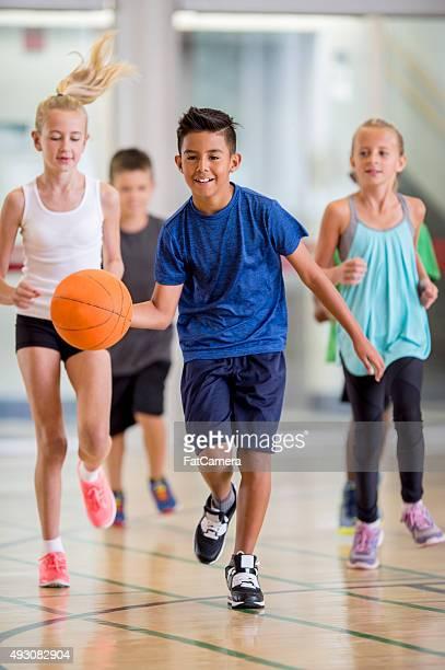 Kinder spielen Sie Basketball im Fitnessraum