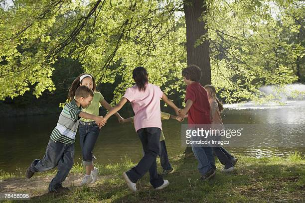 Children playing by tree and river