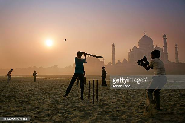 Children playing cricket in front of Taj Mahal at sunrise
