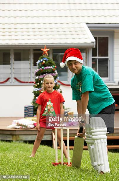 Children (7-12) playing cricket in yard with Christmas decorations