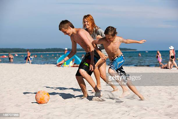 Children playing football on beach with mother