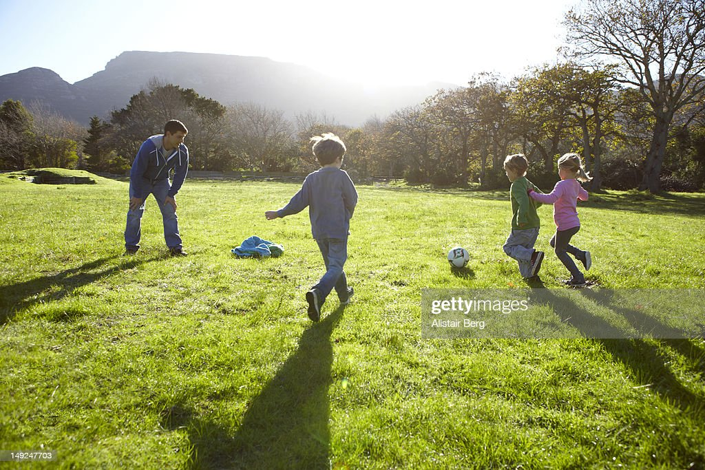 Children playing football together : Stock Photo