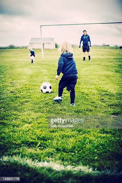 Children playing football with daddy