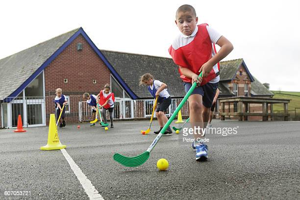 Children playing hockey in playground