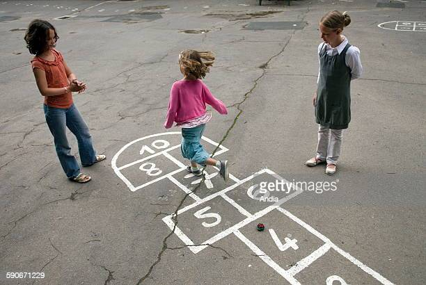 Children playing hopscotch in a schoolyard
