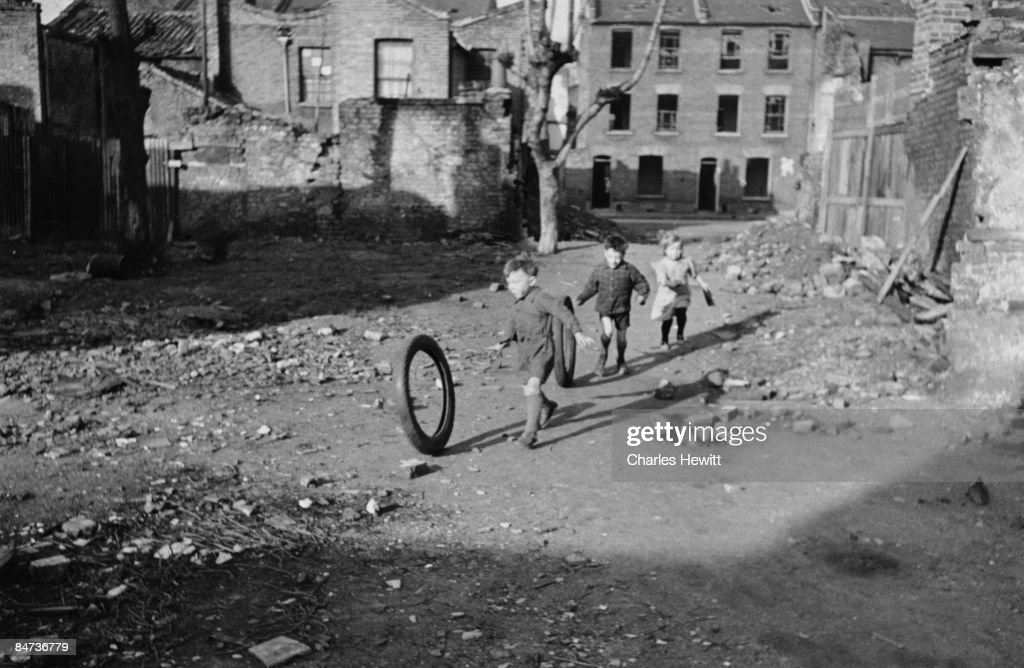 Children playing in an area of bomb-damaged wasteground in Stepney, in the East End of London, 9th March 1946. London County Council plans to transform the area as part of its post-war rebuilding programme. Original Publication : Picture Post - 3092 - The Doomed East End - pub. 1946