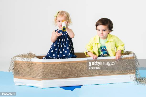 Children playing in cardboard boat