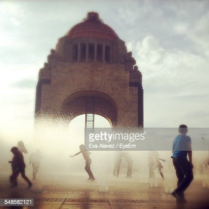 Children Playing In Fountain In Front Of Arched Gate