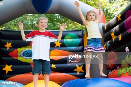 Children playing in inflatable bouncer : Stock Photo