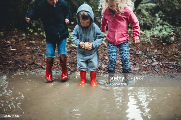 Niños jugando en el charco de lluvia