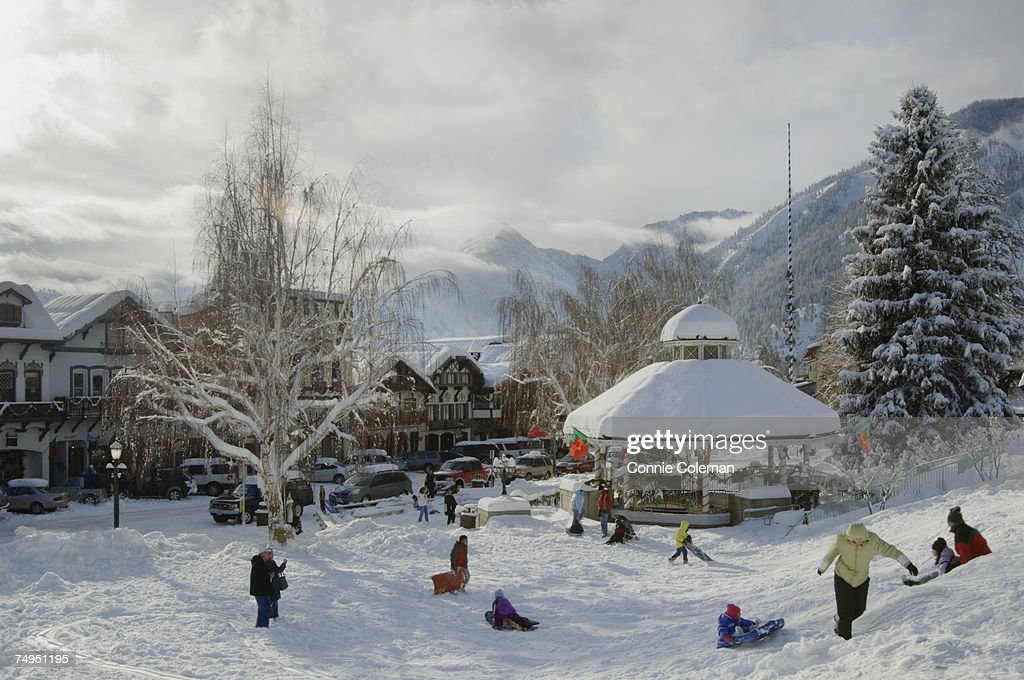 Children playing in snow covered park with gazebo, near mountains : Stock Photo