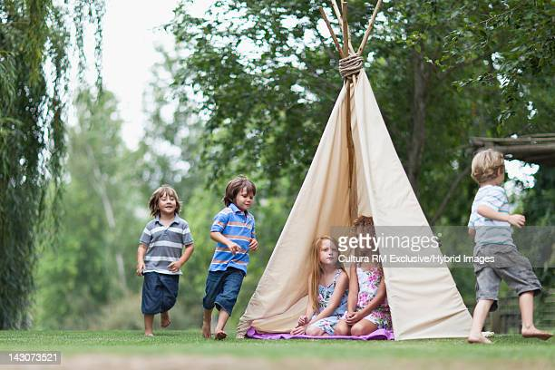 Children playing in teepee outdoors