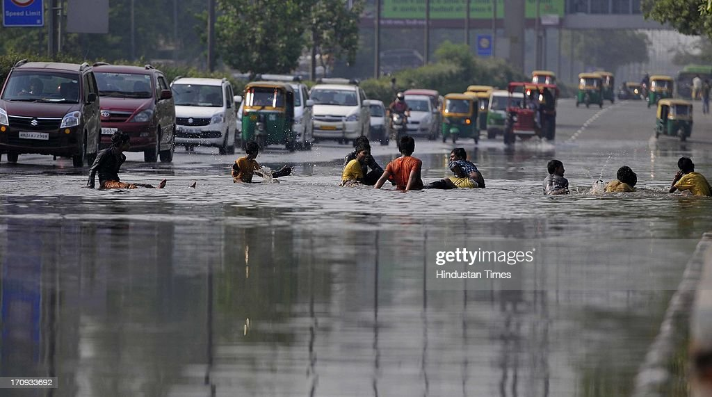 Children playing in the water logged Ring Road on June 20, 2013 in New Delhi, India. Low-lying areas along the Yamuna remained submerged for the second consecutive day though the water level in the river started receding today.