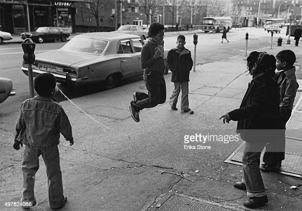 Children playing jumprope in a street in Harlem New York City circa 1982