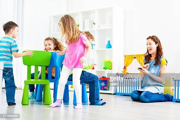 Enfants jouant Musical des chaises à l'intérieur.