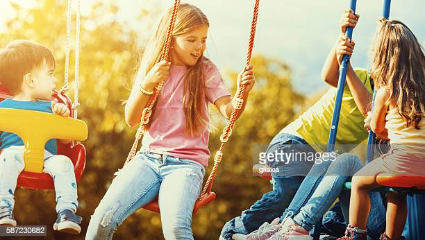 Children playing on a swingset.