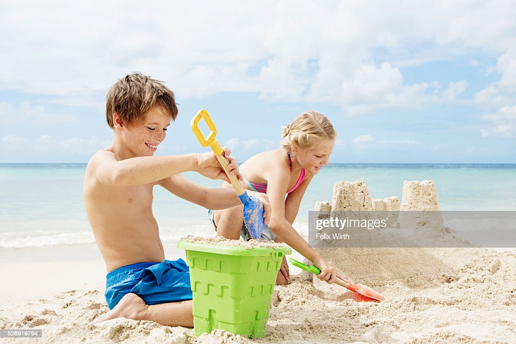 Children (10-12) playing on beach in sand : Stock Photo